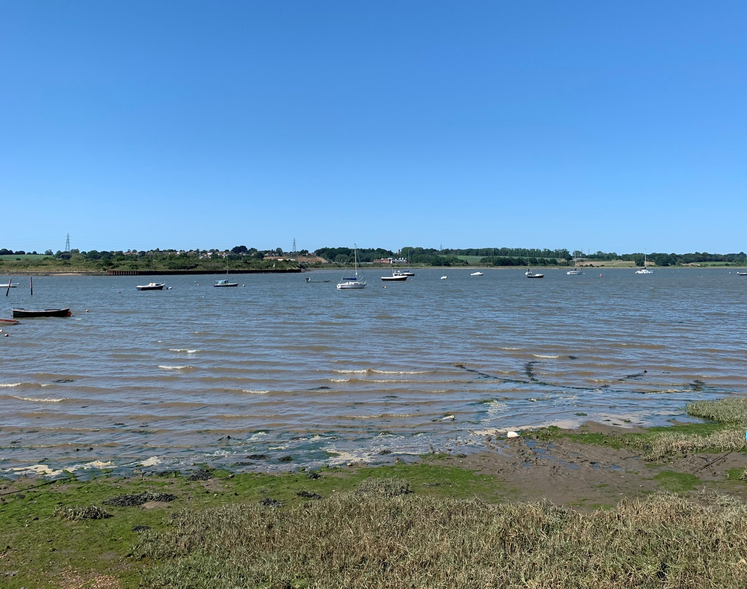 The River Stour at Mistley, with blue skies and boats on the water