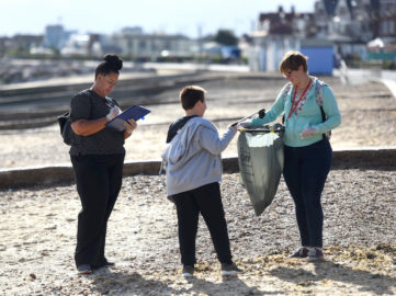 A photo of two women and a boy collecting litter from Felixstowe Beach
