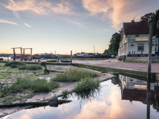 Buildings and boat machinery and Pin Mill with blue skies overhead